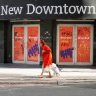 "Old woman in a bright red coat walks past shop windows covered with red paper & graffiti. The sign on the shop says: ""Witness the New Downtown"""