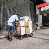 Mailman on a downtown Miami city street resting on his cart loaded with containers of mail