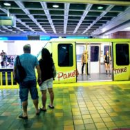 MetroMover at the platform with its doors open; 2 people inside, a couple outside, & a family on the opposite platform