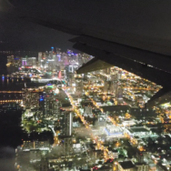 view out the window of airplane showing downtown Miami at night