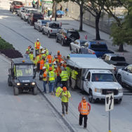 Workers in hardhats and fluorescent vests crowded around food truck at a construction site