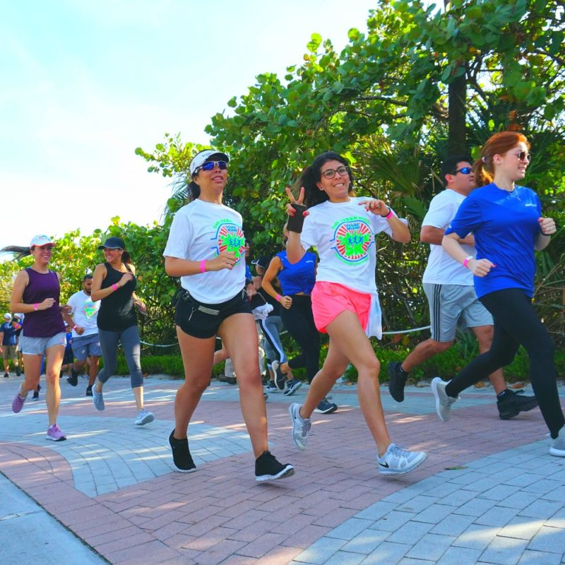 Runners at the Green Mile 5K, with one woman flashing a peace sign to the camera