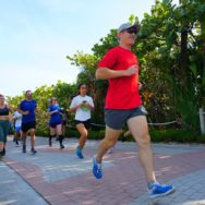 Man in a red shirt running with several other people running behind him