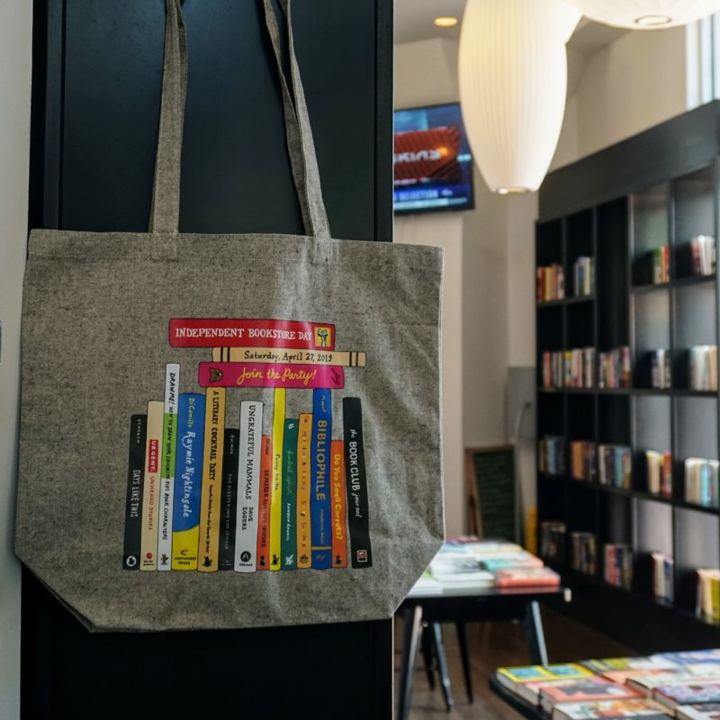 Close up of canvas book bag commemorating the 5th annual Independent Bookstore Day with interior of Books & Books store in the background