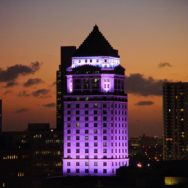 Upper tower of the historic courthouse lit in purple with a dark orange twilight sky and silhouetted skyscapers in the background