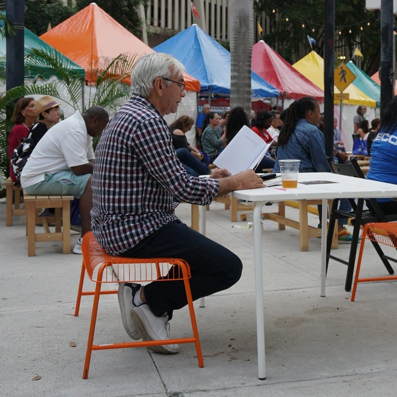 Older man reading a book while sitting at a table in the plaza of Miami Dade College in Downtown Miami