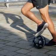 Close up of male soccer player's legs as he maneuvers the ball on the plaza at Bayside Marketplace