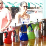 Moka pots (coffee makers) in a variety of bright colors lined up smallest to largest in the shop window. Outside, a woman looks in the window while the background street view is purposely overexposed for contrast.