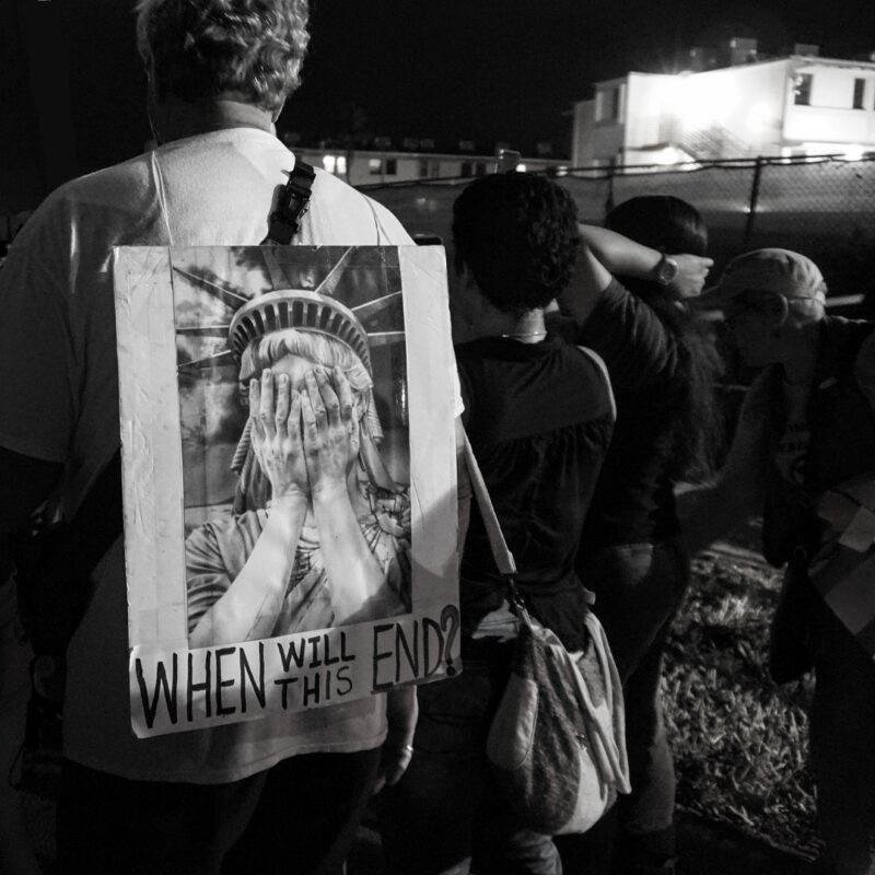 Night vigil; group standing at fence looking at the Homestead Detention Center which is brightly lit in the background. One man wears a sign on his back: a photo of the Statue of Liberty with her head in her hands in shame and the words: When will this end?